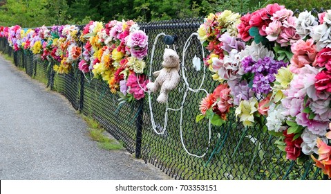 remembering a tragic accident with a teddy bear and flowers on the fence