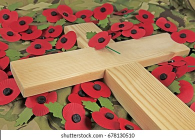Remembrance day poppies surrounding a wooden cross - A wooden cross laying on a green camouflaged cloth surrounded by traditional imitation poppies
