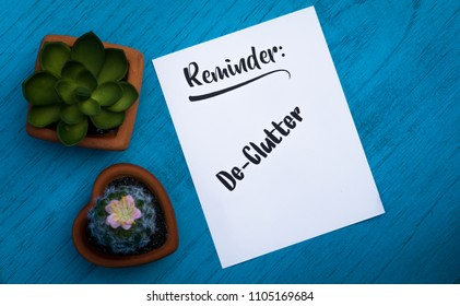 Reminder De-Clutter motivational concept on white paper and blue table flat lay in vintage tones