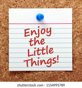 A reminder to Enjoy the Little Things in life in red text on a card pinned to a cork notice board