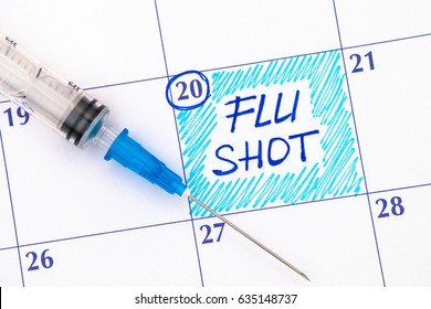 Reminder Flu Shot in calendar with syringe. Close-up.