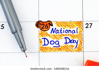 Reminder National Dog Day in calendar with pen. August 26th. Close-up.