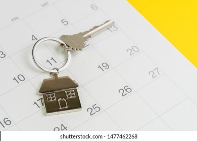 Reminder to pay for mortgage, schedule event or real estate payment day, silver house keyring on white clean calendar, yellow background.