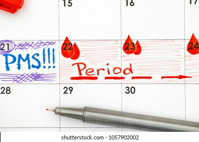 Reminder PMS and Period in calendar with red pen. Closeup.