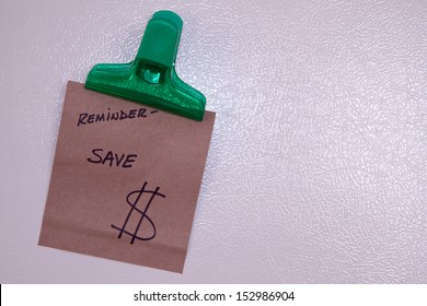 Reminder to save money note in magnetic clip on refrigerator door.
