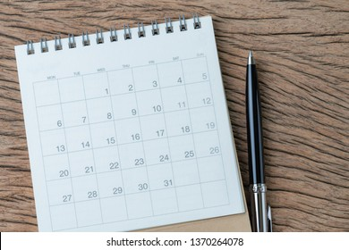 Reminder, schedule or business meeting agenda concept, top view or flat lay black pen with white clean calendar on wooden table.