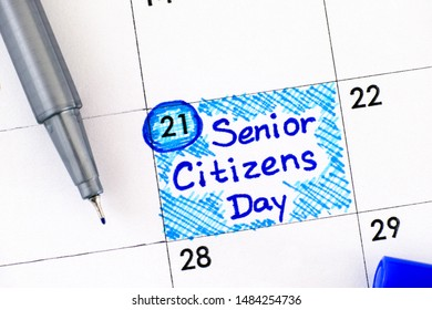 Reminder Senior Citizens Day in calendar with blue pen. August 21st. Close-up.