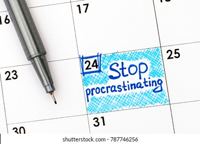 Reminder Stop Procrastinating in calendar with pen. Close-up.