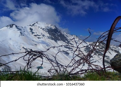 Remnants of the First World War in the alps. Barbed wire lying in front of huge snow covered mountain in the alps