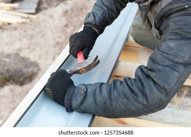 Remodel renovation house concept. Photo of professional workman with hand tool work on incomplete roof, make laying rafters on small wooden building