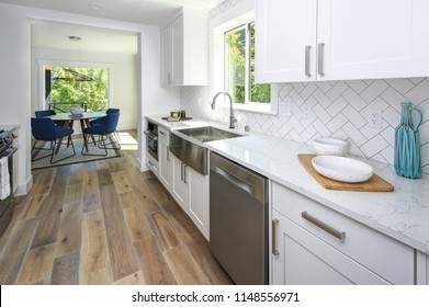 Remodeled kitchen with pure white cabinets, marble countertops, herringbone backsplash and wide-plank hardwood floors.