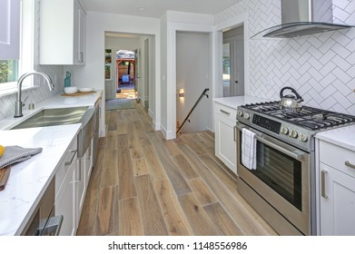 Remodeled kitchen with pure white cabinets, marble countertops, herringbone backsplash and stainless steel appliances.