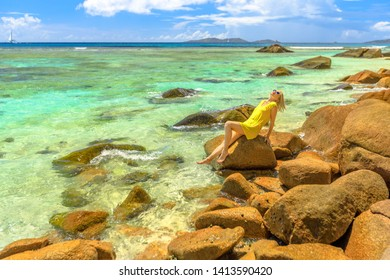 Remote Anse La Blague, southeast of Praslin near Grande and Petite Anse and view of Grande and Petite Soeur. Tourist woman in yellow sunbathing on granite boulder with turquoise waters at Seychelles.