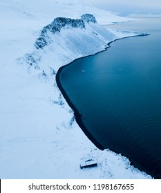 A remote cabin on the wintery coast of Svalbard, lined by a beautiful black stone beach.