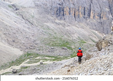 Remote climber descends a trail to the Lasties Valley on Sella massif, Dolomite Alps, Italy