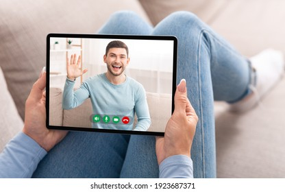 Remote Communication Concept. Young woman making online video call holding and using digital tablet, talking with excited smiling man who waving hello, having virtual conference, lady lying on sofa