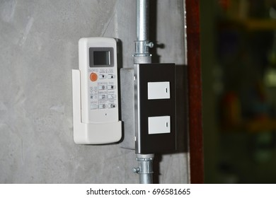 remote control of air conditioner and light switch on loft background.