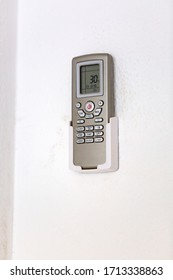 Remote control for air conditioning. Mounted on the wall with a rough surface. Air Conditioner Remote Control. remote control hang on the wall and air conditioner blur background.Black and white tone.