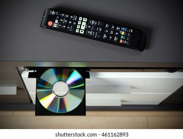 Remote control and Blu-ray or DVD player with inserted disc.