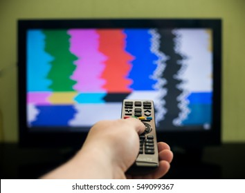 Remote control in hand in front of TV. Couch potato. No signal screen banner.