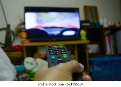 remote control in hand and television monitor