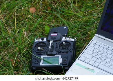 Remote control and laptop are on the green grass in a summer cloudy day.
