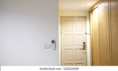 Remote control on the wall beside switches with blur background of door and wooden wardrobe