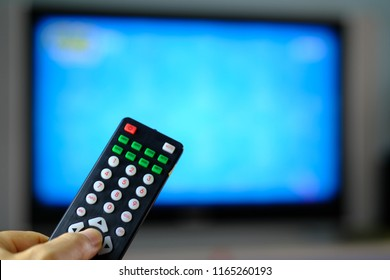 remote control satellite receiver holdig in hand for change channel blurred blue display television background.