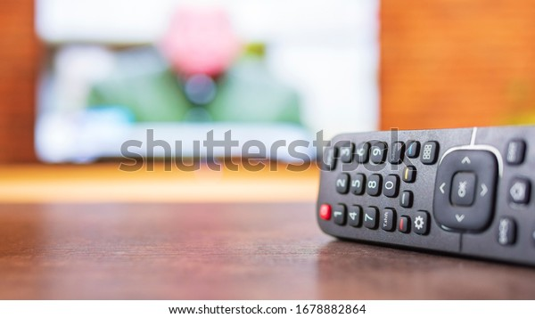 Remote control and TV in the background. Television streaming video concept. Stay home and relax.