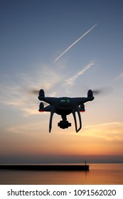 Remote controlled drone equipped with high resolution video camera flying above the sea against a sunset sky