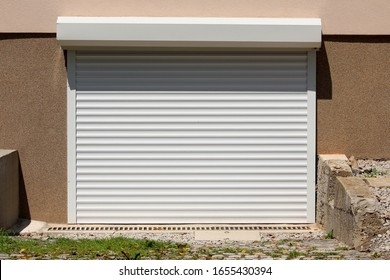 Remote controlled new modern white outdoor garage roll up doors mounted on newly built suburban family house side wall surrounded with unfinished concrete walls and grass covered driveway