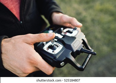 Remote controller in male hands close-up. Unrecognizable man holding transmitter and piloting some vehicle. Drone, rc car or helicopter running. Leisure, hobby, entertainment concept
