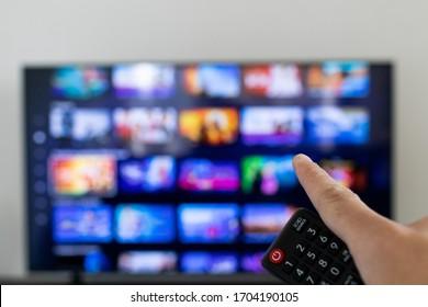 Fernbedienung und TV unscharf im Hintergrund. Video-Streaming-Service-Katalog im Raster unscharf auf smart TV.
