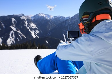 remote controlling a flying drone on winter mountain top