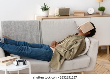 Remote education concept. Bored black teen student with book on his face sleeping on couch at home. African American teenager unwilling to do dull home assignment, napping on sofa with textbook