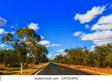 Remote empty B55 highway in remote rural outback of NSW state in Australia on a hot sunny day under blue sky driving between gumtree woods.