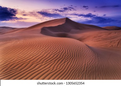 Remote empty lifeless sand desert at sunrise under dark cloudy sky with wind eroded pattern on dunes surface forming land waves.