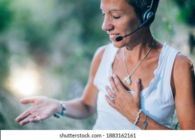 Remote healing therapy. Personal development coach working with a client over the Internet, sitting crosslegged outdoors, sending positive feelings