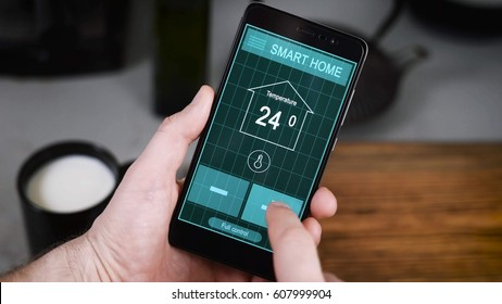 Remote home control system on a digital tablet or phone. Men's hands hold a smartphone with an active application for managing the house. The temperature changes, security systems are monitored