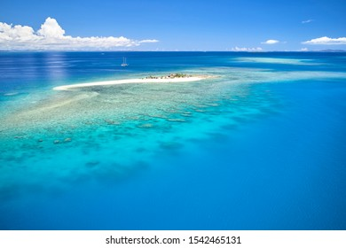 Remote island in Fiji overlooking blue coral reef