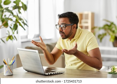remote job, technology and people concept - stressed young indian man in glasses with laptop computer working at home office