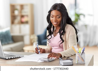 remote job, technology and people concept - happy smiling young african american woman with calculator and papers working at home office