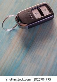 Remote keyless car key on blue wooden background