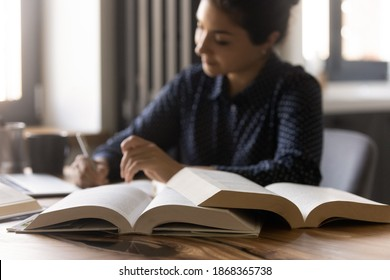 Remote learning. Diligent millennial mixed race female student prepare for exam at home. Confident indian woman write up notes thesis for research report essay. Focus on opened paper books on table