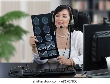 Remote medical specialist in headset is looking at x ray image of brain carefully. Middle aged telemedicine doctor sits at black office desk with keyboard in front of computer monitor