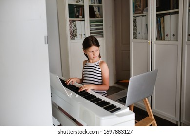 Remote music lesson, a child girl playing the digital piano and looking at a laptop, online learning and video chat on learning to play the piano. Authentic lifestyle in a real interior