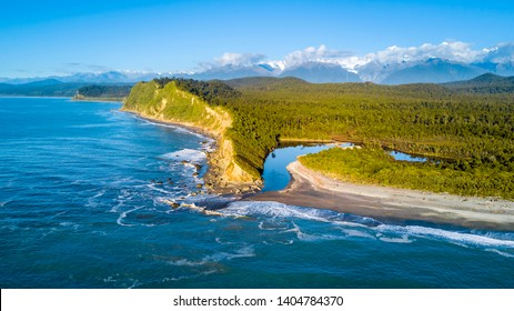 Remote rocky coastline with native forest and snowy mountain peaks on the background. West Coast, South Island, New Zealand