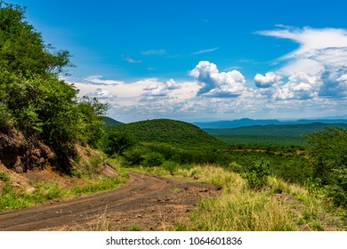 Remote rough, dirt road disappearing into the distance. Looking to Great Rift Valley from the Aberdare Ranges, Kenya. Vegetation is lush. Clouds in blue sky. Copy space.