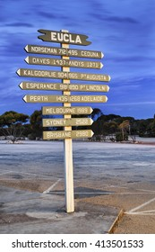 Remote signpost in Eucla, Western Australia with directions and distances to famous destinations around Australia.
