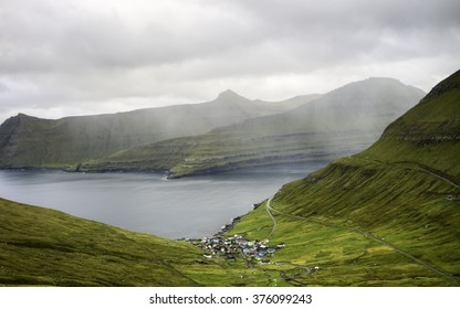 Remote small village surrounded by nature of Faroe Islands. Faroe Islands : typical nordic village overlooking a fjord surrounded by green mountains